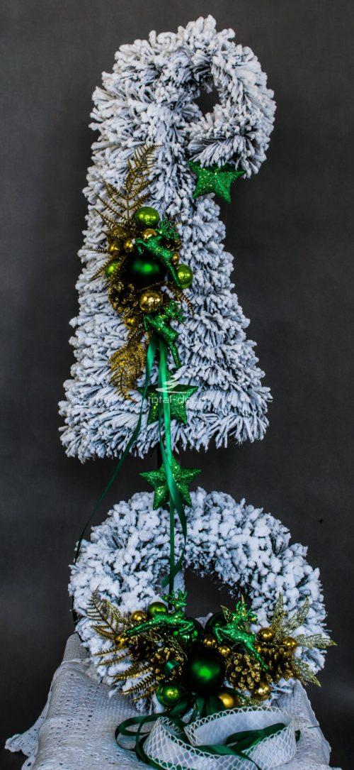 nowoczesny zestaw ośnieżonych dekoracji bożnarodzeniowych nowoczesne ozdoby świąteczne biała choinka na pniu zielone dodatki butelkowa zieleń wianek stroik oprószony śniegiem obielona