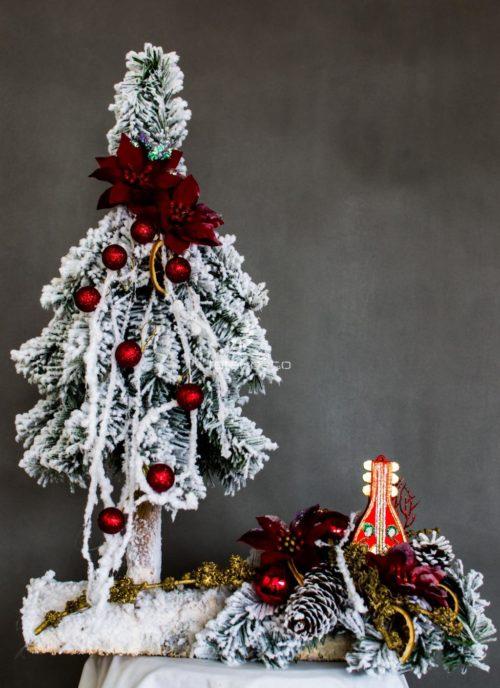 nowoczesny oryginalny stroik choinka ubrana na biało na czerwono na drewnianej podstawie ubrana ozdobiona dekoracja bożonarodzeniowa świąteczna
