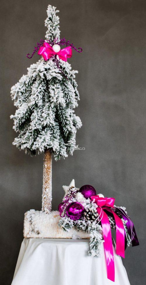 ośnieżona nowoczesna oryginalna choinka i stroik oprószona delikatnym śniegiem ubrana na różowo biało na drewnianej podstawie kokarda bombki dekoracja świąteczna ozdoba bożonarodzeniowa