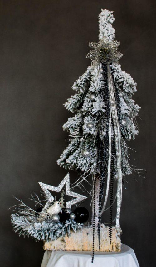 sztuczna choinka i stroik ubrana na biało ośnieżona na pniu nowoczesna ozdoba świąteczna bożonarodzeniowa udekorowana w dodaki w kolorze srebrnym z gwiazdą