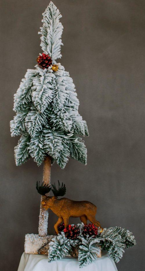 ośnieżona choinka i stroik ubrana na biało na drewnianej podstawie na pniu nowoczesna oryginalna dekoracja świąteczna ozdoba bożonarodzeniowa