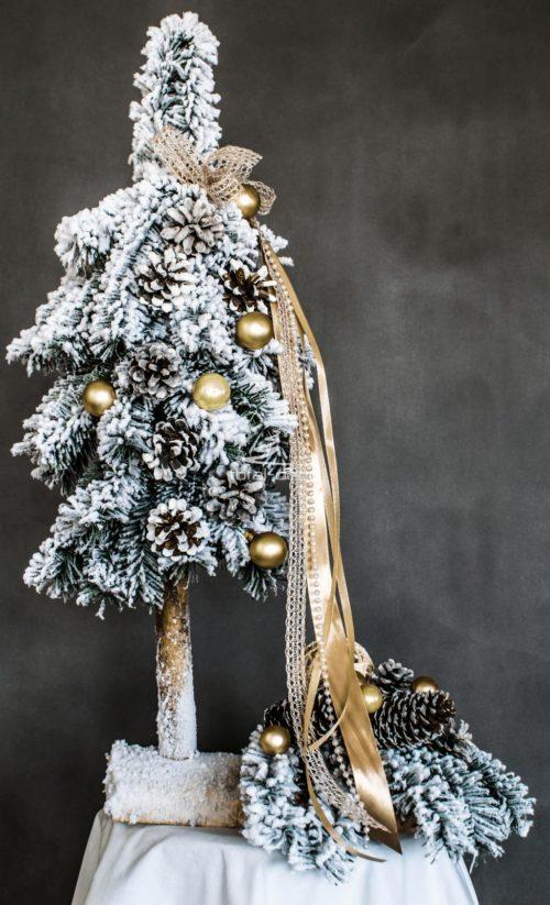 stroik i choinka ubrana na biało na złoto na pniu nowoczesna białą oprószona śniegiem