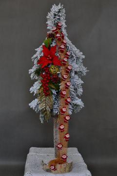 Choinka ośnieżona na biało ozdobiona dekoracjami złoto czerwonymi z mnustwem mikołajków świątecznych