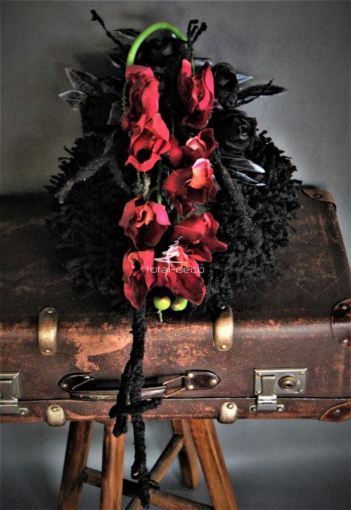 Dekoracja nagrobna stroik na cmentarz na orycinalnym flokowanym czarnym wianku z dekoracyjnymi czarnymi gałęźmi i czarnymi różami i liśćmi. Harakteru nadaje piękne gumowe cymbidium w kolorze wina.