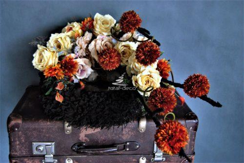 Dekoracja nagrobna stroik na cmentarz wykonany na dużym ciemno brązowym wianku z kwiatami w kolorach rudości i budyniu z grubymi dekoracyjnymi gałęźmi w kolorze wianka