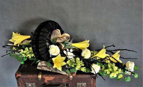 dekoracja nagrobna stroik na cmentarz duża ciężka kompozycja na brzozowej podstawie z brzozowymi polanami i grubym czarnym wiankiem z kwiatami w kolorze żółtym i budyniowym zachowana w naturalistycznym klimacie z surowymi srcami z brzozy, za