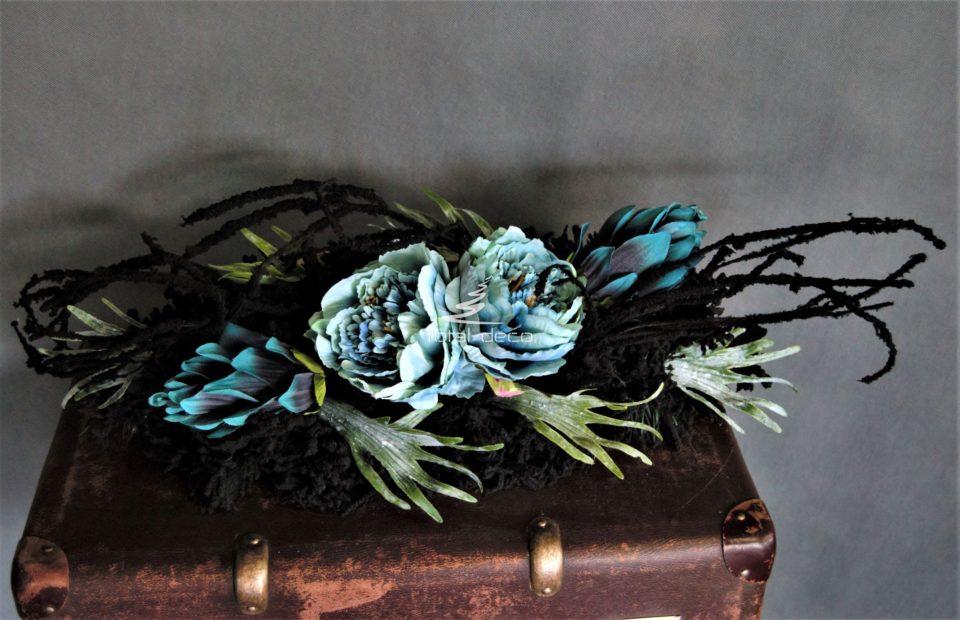 Dekoracja nagrobna stroik na cmentarz nowoczesna forma na czarnym podkładzie z czarnymi gałązkami ozdobiona zgaszonymi kwiatami w kolorze morskim i dodatkami wysoliej jakości