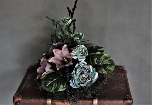 Dekoracja nagrobna stroik na cmentarz na czarnym okrągłym podkładzie z czarnymi dekoracyjnymi gałązkami i kwiatami w zgaszonym różu i zimnym niebieskawym