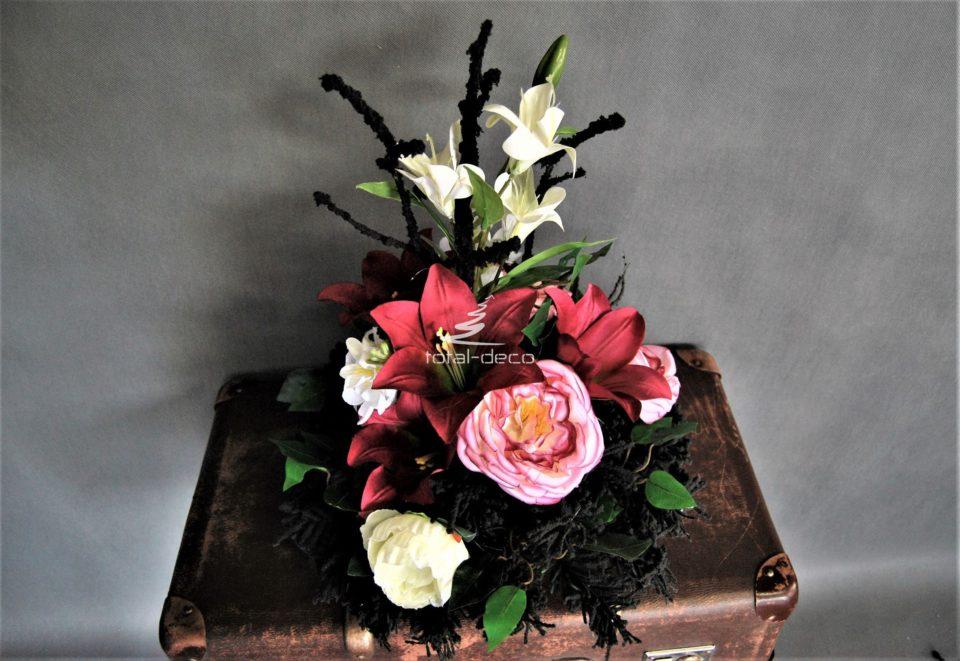 Dekoracja nagrobna stroik na cmentarz na okrągłym czarnym podkładzie z czarnymi gałązkami i kwiatami biało różowymi