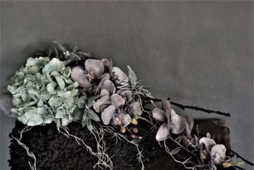 Dekoracja nagrobna stroik na cmentarz na oryginalnej czarnej bazie pokaźnych rozmiarów z kwiatami w modnych rozmytych kolorach i pięknymi dodatkami w kształcie łezki