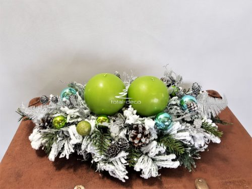 Stroik świąteczny na białej ośnieżonej bazie z zielonymi świecami pięknie udekorowany niebieskimi bombkami i srebrnymi dodatkami ośnieżony stroik bożonarodzeniowy oryginalna ozdoba świąteczna ze świecami stroik z naturalnymi dodatkami szyszkami