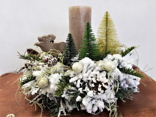 Stroik dekoracja świąteczna ośnieżona zachowana w leśnym rustykalnym klimacie udekorowana świecą , drewnianym łosiem i małymi choinkami ubrana ośnieżony stroik bożonarodzeniowy oryginalny nowoczesny