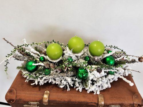 Stroik dekoracja bożonarodzeniowa obsypana puchatym białym śniegiem z zielonymi świecami i srebrno zielonymi dekoracjami nowoczesna ozdoba świąeczna kolor zielony ośnieżona ubrana udekorowana unikatowa