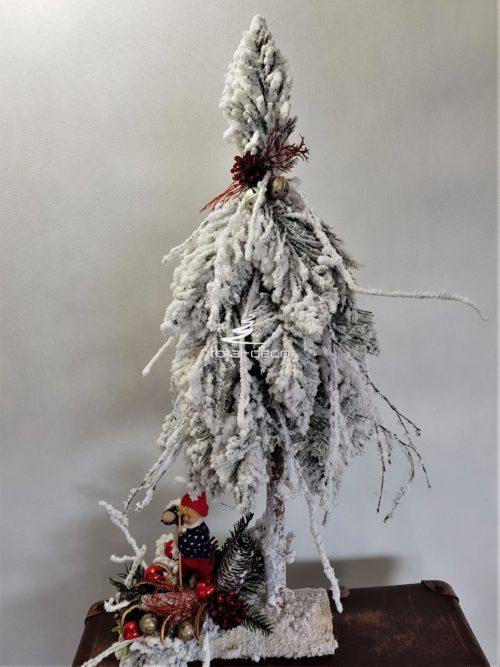 Ubrana choinka ze stroikiem ośnieżona z zimową dziewczynką w czapce piękna dekoracja świąteczna na pniu razem ze stoikiem ośnieżona śnieżna ozdoba