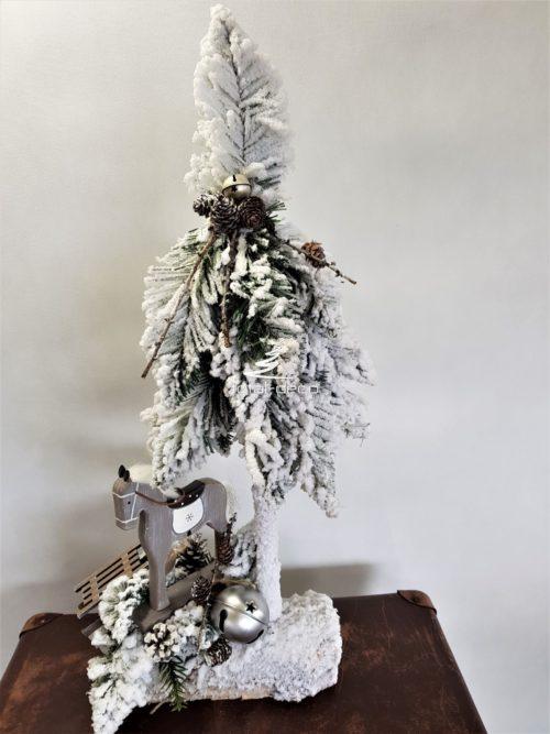 Dekoracyjna choinka ze stroikiem obsypana śniegiem ozdobiona drewnianym koniem w odcieniach szarośc metalową bombkom dzwonkiem i naturalnymi dodatkami ośnieżona ozdoba dekoracja świąteczna bożonarodzeniowa oryginalna modna ozdoba świąteczna choinka ubrana na pniu