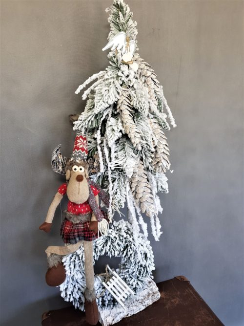 Piękna choinka ze stroikiem ośnieżona na biało z siedzącym dużym świątecznym reniferem na wianku