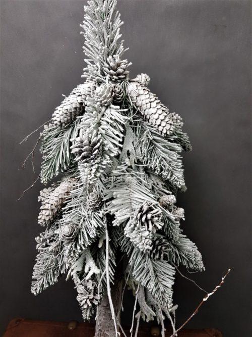 naturalna choinka ośnieżona żywa nowoczesna na pniu z dodatkiem naturalnych szyszek ozdoba bożonarodzeniowa świąteczna choinka na drewnianej podstawie